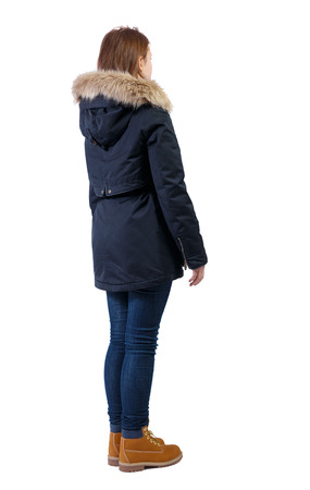Back view woman in winter jacket. Standing young girl in parka. Rear view people collection.  backside view of person.  Isolated over white background. The girl in boots and a black jacket looks thoughtfully sideways.