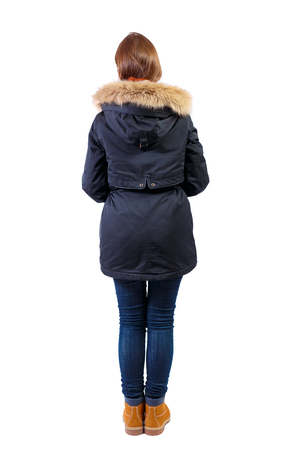 Back view woman in winter jacket  looking up.  Standing young girl in parka. Rear view people collection.  backside view of person.  Isolated over white background. The girl in boots and a black jacket is looking forward.
