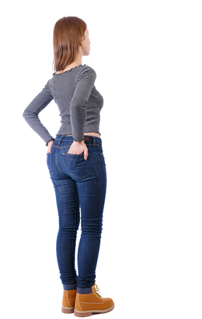 Back view of a woman in jeans.  girl  watching. Rear view people collection.  backside view of person. Isolated over white background. Girl in a striped T-shirt stuck her hands in the back pockets of pants Stockfoto