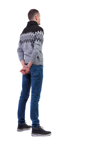 Back view of a stylish man in a knitted sweater. Rear view people collection.  backside view of person.  Isolated over white background. The guy in the winter warm sweater stands sideways with his hands behind his back.