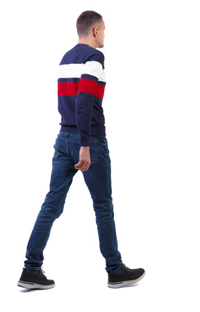 Back view of going  handsome man in sweater. walking young guy . Rear view people collection.  backside view of person.  Isolated over white background. A tall, slender man in jeans and a striped sweater is slowly moving forward.