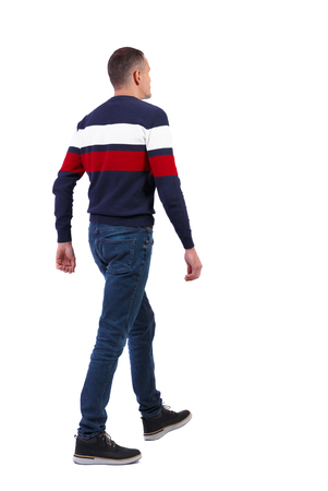 Back view of going  handsome man in sweater. walking young guy . Rear view people collection.  backside view of person.  Isolated over white background. A tall, slender man in jeans and a striped sweater is waving his arms. Stock Photo
