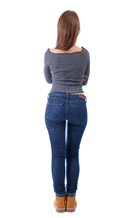 Back view of a woman in jeans.  girl  watching. Rear view people collection.  backside view of person. Isolated over white background. A young long-haired girl stands with her arms folded.