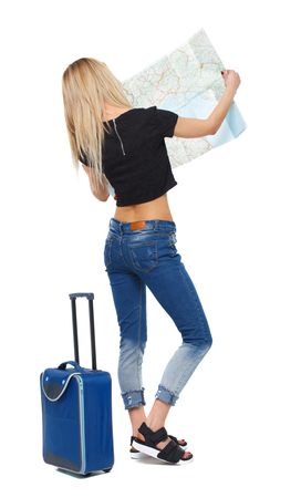 Back view of a woman with a map and a suitcase. backside view of person.  Rear view people collection. Isolated over white background. Tourist woman in summer clothes is carefully considering the map.