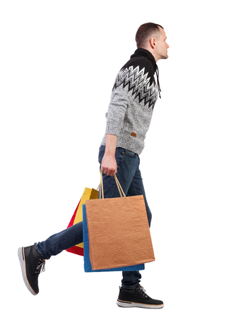 Side view of going man with shopping bags. guy in motion. backside view of person. Rear view people collection. Isolated over white background. The guy in the warm sweater is shopping.