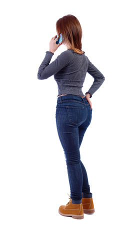 back view of a woman talking on the phone. backside view of person.  Rear view people collection. Isolated over white background. A skater girl is standing talking on a smartphone with a hand in her back jeans pocket.