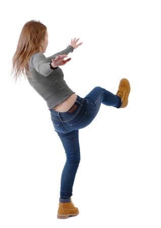 Jeune femme en équilibre. ou esquiver la chute de la femme. Collection de personnes vue arrière. vue arrière de la personne. Isolé sur fond blanc. Une jeune fille bat du pied. Banque d'images