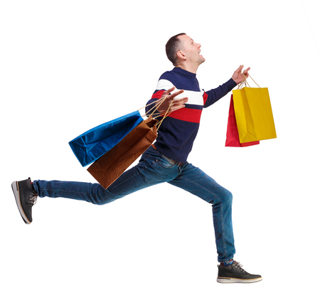 Side view of a man in a sweater with shopping bags that runs. backside view of person.  Rear view people collection. Isolated over white background. The guy in the striped sweater happily runs through shopping. runner finishes Foto de archivo
