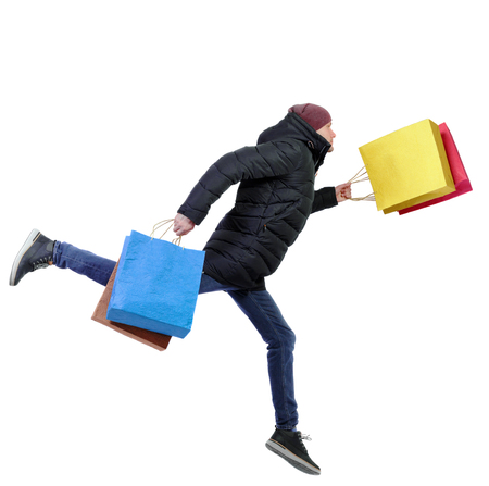 Side view of a man in winter jacket with shopping bags that runs. backside view of person.  Rear view people collection. Isolated over white background. Buyer in a warm jacket and hat in a long jump with shopping bags.