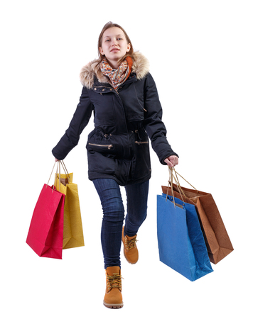 Front view of a happy woman in a jacket with shopping bags that runs. beautiful brunette girl in motion.  backside view of person.  Rear view people collection. Isolated over white background. A girl in a warm jacket with fur runs into the frame with the purchases.
