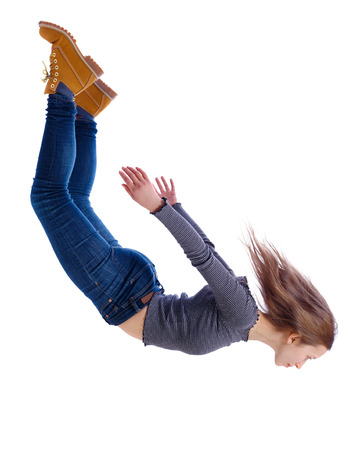 Side view of woman in zero gravity or a fall. girl is flying, falling or floating in the air. Side view people collection. side view of person. Isolated over white background. The girl in jeans falls down in a free fall. Foto de archivo