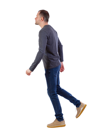 Side view of going  handsome man . walking young guy . Rear view people collection.  backside view of person.  Isolated over white background. A young guy in a gray sweater goes sideways.