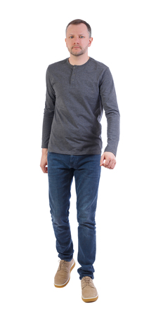 Side view of going  handsome man. walking young guy.  Isolated over white background. A man in a gray sweater enters the frame.