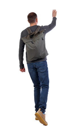 Back view of a walking man with a bag pointing his hand up. backside view of person.  Rear view people collection. Isolated over white background. The guy in the gray jacket goes ahead with a backpack showing his hand forward. Stock Photo