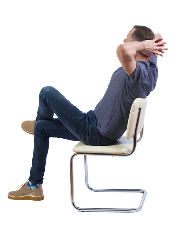 Side view of a man sitting on a chair. Rear view people collection.  backside view of person.  Isolated over white background. A man in a chair sits sprawled and his hands behind his head.