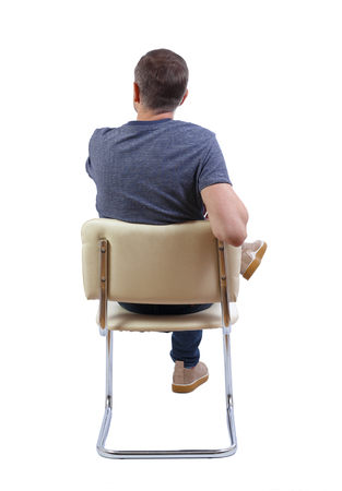 Back view of a man sitting on a chair. Rear view people collection.  backside view of person.  Isolated over white background. The guy comfortably sprawled on a chair.