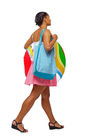 Side view of an African-American with a beach bag that goes to the side. backside view of person.  Rear view people collection. Isolated over white background. Black girl carries a rubber ring and bag to the beach Фото со стока