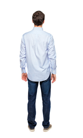 Back view of a stylish man. Rear view people collection.  backside view of person.  Isolated over white background. Guy in in a white not tucked in shirt looks ahead. Фото со стока