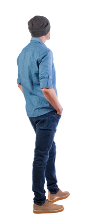 Back view of man in gray hat. Standing young guy. Rear view people collection.  backside view of person.  Isolated over white background. The guy in the cap is worth his hands in his pockets.
