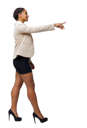 Side view of a black African-American in a suit that goes and points with his hand. backside view of person.  Rear view people collection. Isolated over white background. young business woman walks by showing an arm forward.