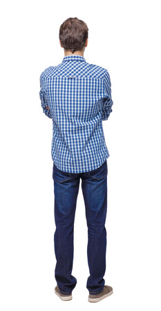 Back view of man in dark jeans. Standing young guy. Rear view people collection.  backside view of person.  Isolated over white background. The guy in sneakers and shirt stands with his arms crossed. 스톡 콘텐츠
