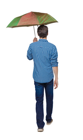 young man walking under an umbrella. Rear view people collection.  backside view of person. Isolated over white background. A young guy in a plaid shirt goes ahead. Stock Photo