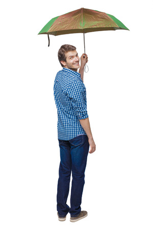 Back view of a man with an umbrella. Rear view people collection.  backside view of person.  Isolated over white background. A young guy in a plaid shirt is smiling while holding an umbrella. Фото со стока