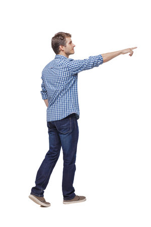 Back view of a man walking with a pointing hand. going guy showing.  backside view of person.  Rear view people collection. Isolated over white background. A young guy in a plaid shirt passes by pointing to the target.
