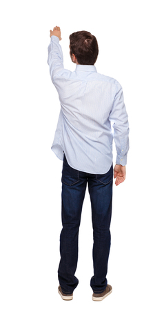Back view of a man in jeans points his hand upwards. Rear view people collection. backside view of person. Isolated over white background. The guy in the white shirt stands showing up. Imagens