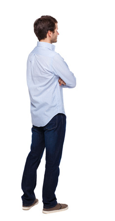 Back view of man in dark jeans. Standing young guy. Rear view people collection.  backside view of person.  Isolated over white background. The guy in the white shirt stands with his arms folded.