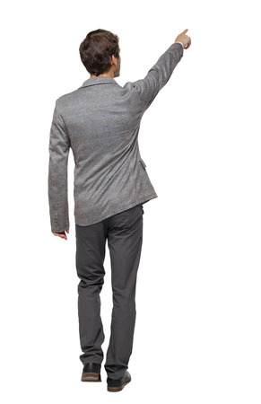 Back view of walking pointing business man. gesticulating young guy in suit. Rear view people collection.  backside view of person.  Isolated over white background. A young businessman in a tweed suit walks away showing his thumb up.