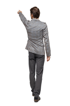 Back view of walking pointing business man. gesticulating young guy in suit. Rear view people collection. backside view of person. Isolated over white background. A young businessman in a tweed suit conducts a tour.
