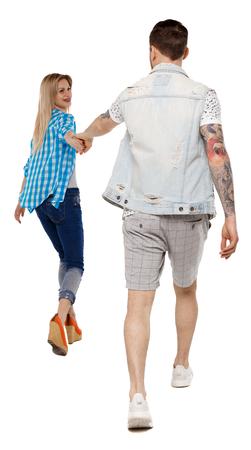 Rückansicht des gehenden Paares. zu Fuß freundliches Mädchen und Kerl, die Händchen halten. Rückansicht Menschen Sammlung. Rückansicht der Person. Getrennt über weißem Hintergrund. Glückliches Mädchen zieht die Hand ihres Freundes. Standard-Bild