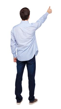 Vista posterior de un hombre mostrando el pulgar hacia arriba. Colección de personas de vista trasera. vista trasera de la persona. Aislado sobre fondo blanco. El tipo de la camisa blanca levantó la mano en señal de aprobación. Foto de archivo