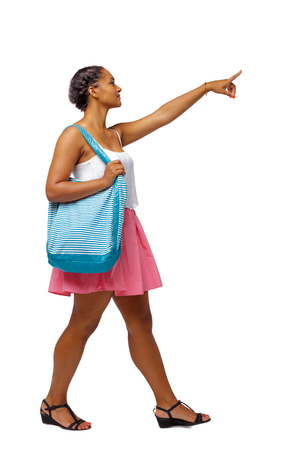 Side view of pointing African-American with a beach bag that goes to the side. backside view of person.  Rear view people collection. Isolated over white background. Young black girl with a beach bag showing a finger to the target 免版税图像