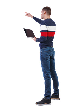 Back view of a pointing man who is standing with a laptop. Rear view people collection.  backside view of person.  Isolated over white background. An engineer with a laptop holds a presentation. Фото со стока