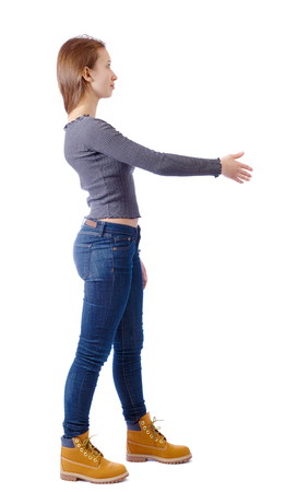 Back view of a woman who stretches his hand for a handshake. Rear view people collection. backside view of person. Isolated over white background. Girl in jeans stretches a hand welcoming.