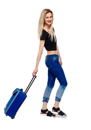 Seitenansicht der gehenden Frau mit Koffer. Mädchen in Bewegung. Rückansicht der Person. Rückansicht-Menschensammlung. Getrennt über weißem Hintergrund. Glückliche Blondine rollt einen Koffer.