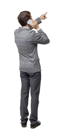 back view of pointing business man in suit  talking on mobile phone. rear view people collection. Isolated over white background. backside view of person. A businessman put a smartphone to his ear explains something.