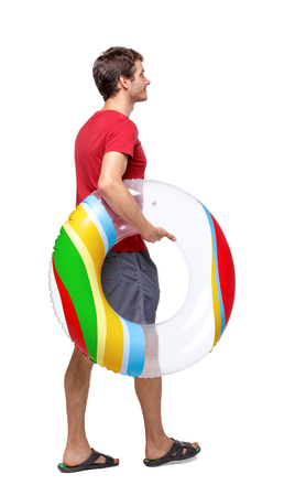 Side view of man with a beach bag that goes to side. backside view of person. Rear view people collection. Isolated over white background. The guy is holding a circle in his hand for the pool. Imagens