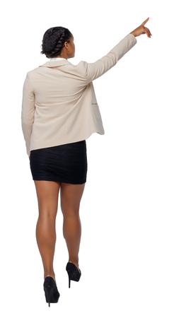 Rückansicht eines schwarzen Afroamerikaners in einem Anzug, der mit seiner Hand geht und zeigt. Rückansicht der Person. Rückansicht Menschen Sammlung. Getrennt über weißem Hintergrund. Ein schwarzes Mädchen in einer Jacke unterwegs führt eine Tour durch. Standard-Bild