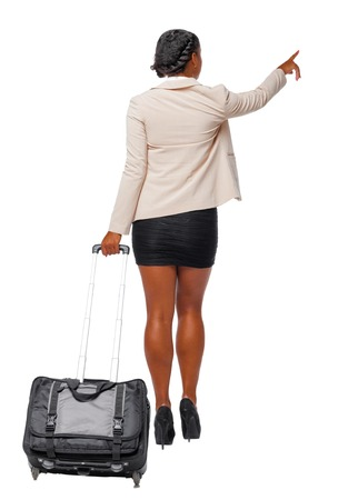 Back view of a black African-American in formal attire walking with a suitcase and pointing hand forward. business woman in motion.  backside view of person.  Rear view people collection. Isolated over white background. Black business woman leaves showing hand up. Standard-Bild