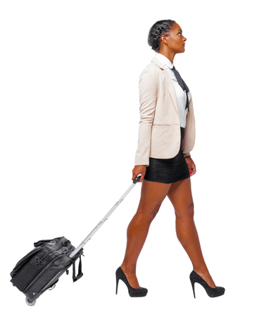 Side view of black African-American in formal attire walking with a suitcase. business woman in motion. backside view of person. Rear view people collection. Isolated over white background. Business woman traveler rolls the suitcase. Standard-Bild