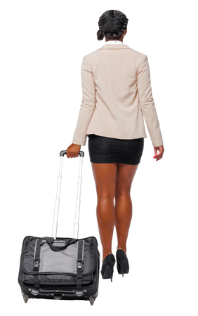 Back view of black African-American in formal attire walking with a suitcase. business woman in motion.  backside view of person.  Rear view people collection. Isolated over white background. Business woman traveler wheels the suitcase departing into the distance. Banque d'images