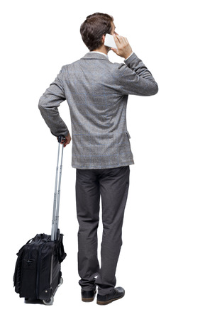 Back view of business man with suitcase talking on the phone. Standing young girl. Rear view people collection.  backside view of person. Isolated over white background. Young traveler with a suitcase talking on a white phone.