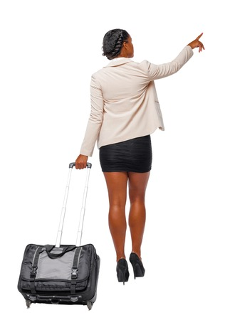 Back view of a black African-American in formal attire walking with a suitcase and pointing hand forward. business woman in motion. backside view of person. Rear view people collection. Isolated over white background. Business woman traveler with a suitcase goes into the distance studying something from the side.