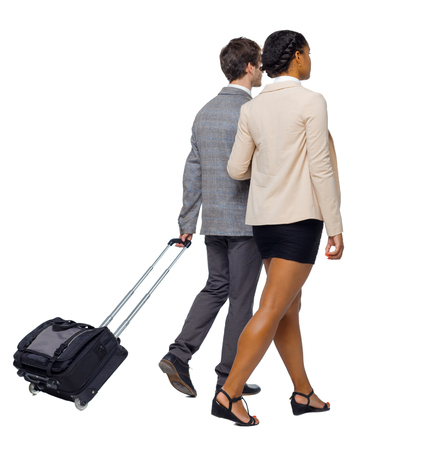 Back view of interracial going couple with suitcase. Rear view people collection. backside view of person. Isolated over white background. Business partners at the airport. Stock Photo