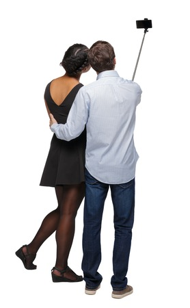 Back view of an interracial couple that makes selfie on selfie stick. beautiful friendly girl and guy together. Rear view people collection.  backside view of person. Isolated over white background. Newlyweds are photographed on the background of attractions.
