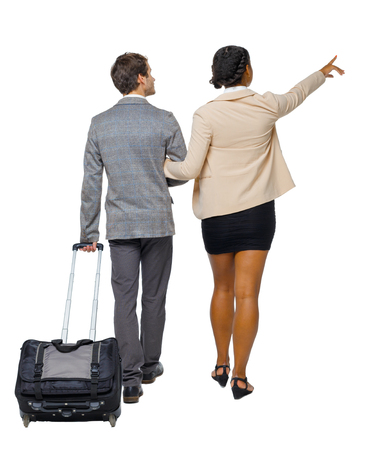 Back view of pointing interracial going couple with suitcase. Rear view people collection. backside view of person. Isolated over white background. Husband and wife on a trip looking at the sights. Imagens