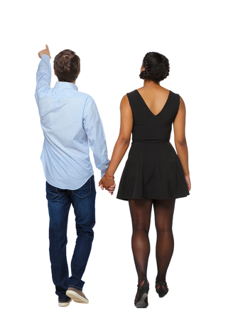 Back view of interracial going couple who points somewhere. walking friendly girl and guy holding hands. Rear view people collection. backside view of person. Isolated over white background. The guy leads the black girl by the hand.